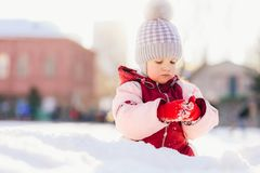 Little baby is sitting on the snow at sunset. Little kid plays in the street in winter Stock Image