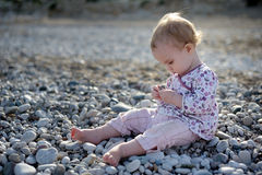 Little baby sitting on the stones. Little baby sitting by the sea on the stones and playing with them Royalty Free Stock Image