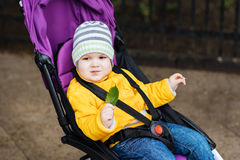 Little baby is sitting in a stroller Royalty Free Stock Photo
