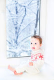 Little baby sitting at window to snowy garden Royalty Free Stock Photo