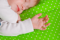 Little baby sleeping on green cushion Stock Photos