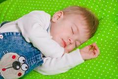 Little baby sleeping on green cushion Stock Photo