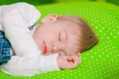 Little baby sleeping on green cushion Stock Image