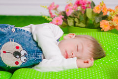 Little baby sleeping on green cushion Royalty Free Stock Photos
