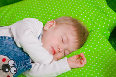 Little baby sleeping on green cushion Stock Images