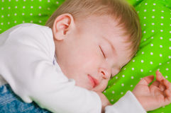 Little baby sleeping on green cushion Royalty Free Stock Photography