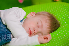 Little baby sleeping on green cushion Royalty Free Stock Image