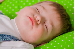 Little baby sleeping on green cushion Stock Photography