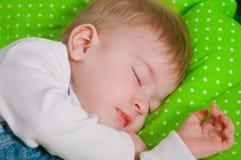 Little baby sleeping on green cushion Royalty Free Stock Photo