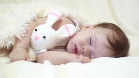 Little baby is sleeping in his crib embracing toy hare.  stock video footage