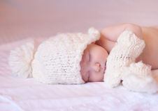 Little baby sleeping with knitted hat and mittens. Little cute baby sleeping on the white covered bed with knitted hat and mittens Royalty Free Stock Photography