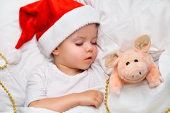 Little baby sleeping on white linen in the Santa hat with his toy pig, wich is the symbol of the year 2019. Sleeping baby new year night royalty free stock photography