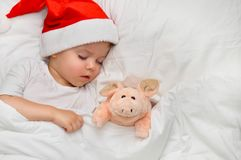 Little baby sleeping on white linen in the Santa hat with his toy pig, wich is the symbol of the year 2019. Sleeping baby new year night stock images