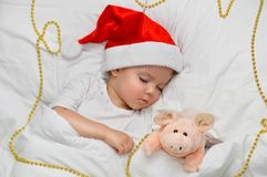 Little baby sleeping on white linen in the Santa hat with his toy pig, wich is the symbol of the year 2019. Sleeping baby new year night royalty free stock images
