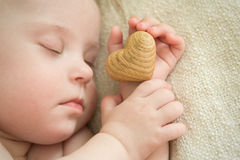 Little baby is sleeping with a wooden heart in hand