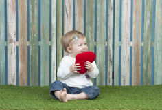 Little baby with small red heart pillow Stock Images
