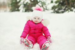 Little baby on the snow in the winter. Day Royalty Free Stock Photo