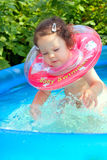 Little baby splashing in waterpool. With blue water Stock Photo