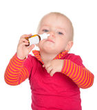 Little baby girl spraying herself nose spray  on white Royalty Free Stock Images