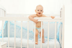 Little baby standing on the bed home in room Royalty Free Stock Images