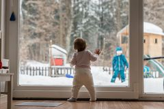 Little baby standing watching a sibling outdoors Royalty Free Stock Photos