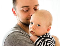 A little baby in a striped shirt in the arms of his father, looks thoughtfully Stock Photography