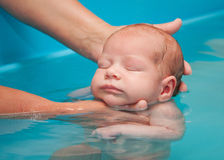 Little baby swimming. In water royalty free stock photography