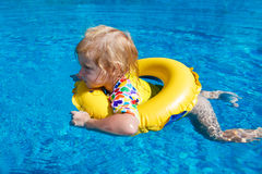 Little baby swimming in a pool. On swimming ring stock photo