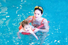 Little baby swimming in a pool with her mother Stock Images
