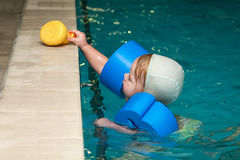 Little baby swimming in water. With toys stock image