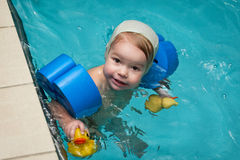 Little baby swimming in water. With toys royalty free stock photography