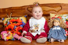Little baby with a tail sits on a sofa with embroidered pillows and toys stock photo
