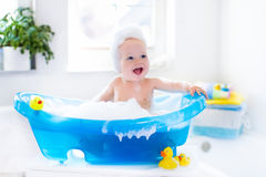 Little baby taking a bath. Happy laughing baby taking a bath playing with foam bubbles. Little child in a bathtub. Smiling kid in bathroom with colorful toy duck Stock Photography