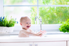 Little baby taking bath. Baby taking bath in kitchen sink. Child playing with foam and soap bubbles in sunny bathroom with window. Little boy bathing. Water fun stock photography