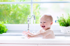Little baby taking bath. Baby taking bath in kitchen sink. Child playing with foam and soap bubbles in sunny bathroom with window. Little boy bathing. Water fun Royalty Free Stock Photo