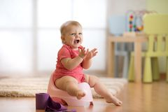 Little baby girl claps sitting on chamberpot in nursery room stock photos