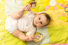 Little baby touching her feet aerial view Royalty Free Stock Image