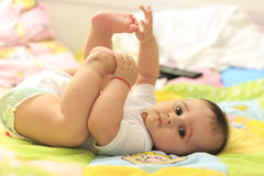 Little baby touching her feet Stock Photo