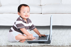 Little baby using a laptop Stock Photos