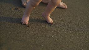 A little baby walking barefoot on the sand. Mother teaches the child to walk.