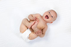 Little baby wearing a diaper. Funny little baby wearing a diaper playing on a white knitted blanket in a sunny nursery. Child after bath or shower on a fresh royalty free stock image