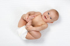 Little baby wearing a diaper. Funny little baby wearing a diaper playing on a white knitted blanket in a sunny nursery. Child after bath or shower on a fresh stock photo