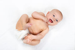 Little baby wearing a diaper. Funny little baby wearing a diaper playing on a white knitted blanket in a sunny nursery. Child after bath or shower on a fresh stock image