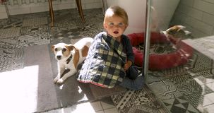 Child and dog sitting on floor. Little baby wearing striped onesies holding pillow and dog sitting on tile floor looking at camera stock video footage