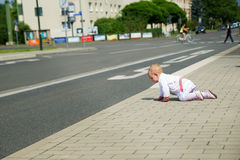 Little baby in white clothes crawling along the  road Stock Photo