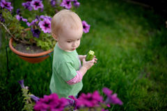 Little baby in the yard having some cucumber Royalty Free Stock Photo