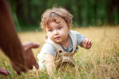 The little baby or year-old child on the grass in sunny summer day. The concept children's months, happy child playing Stock Images