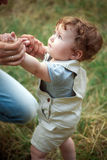 The little baby or year-old child on the grass in sunny summer day. stock photos