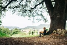 Little backpacker traveler rests under big tree on country road Royalty Free Stock Image