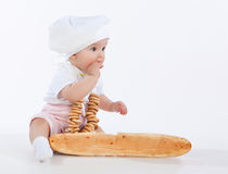 Little baker baby girl with a long loaf and bagels. Royalty Free Stock Photos